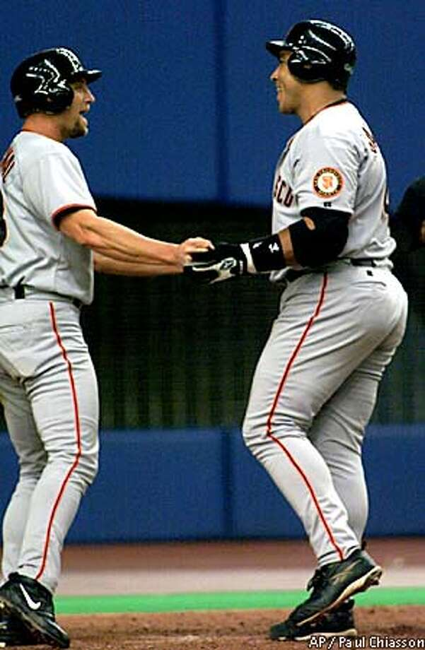 San Francisco Giants' Andres Galarraga is greeted at the plate by teammate John Vander Wal after hitting a two-run home run off Montreal Expos pitcher Britt Reames during eighth inning NL action Thursday Aug. 23, 2001, in Montreal. (AP Photo/Paul Chiasson) Photo: PAUL CHIASSON