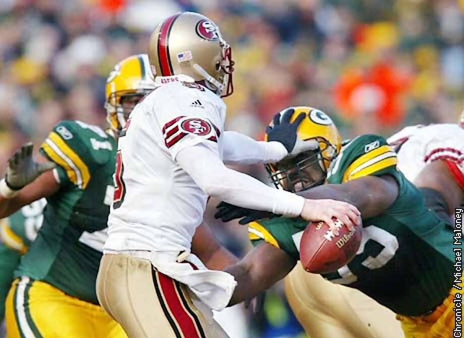 49ers Jeff Garcia holds off #55 Bernardo Harris in the 2nd quarter.  SF 49ers vs Greenbay Packers at Lambeau Field in Green Bay. Packers won 25-15.  CHRONICLE PHOTO BY MICHAEL MALONEY Photo: MICHAEL MALONEY