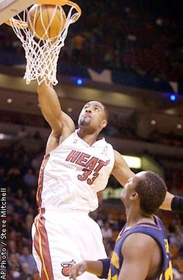Miami Heat's Alonzo Mourning, left, slam dunks above Golden State Warriors' Danny Fortson during the first half Sunday, Jan. 6, 2002, in Miami. (AP Photo/ Steve Mitchell) Photo: STEVE MITCHELL