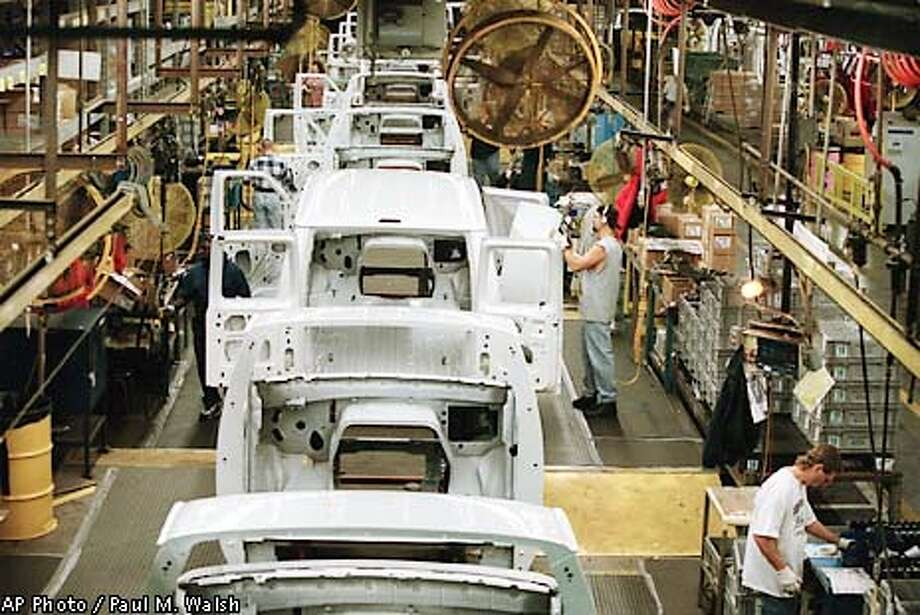 Workers inspect doors of Econoline vans as they leave the paint shop at the Avon Lake, Ohio, Ford assembly plant Nov. 9, 2001. Analysts predict Ford Motor Co. will announce job cuts of anywhere from about 12,000 to 20,000 Friday morning, Jan. 11, when it makes public its long-awaited restructuring plan. The plant assembles the Ford Mercury Villager, Nisson Quest, and the Ford Econoline Vans. (AP Photo/The Morning Journal, Paul M. Walsh) Photo: PAUL M. WALSH