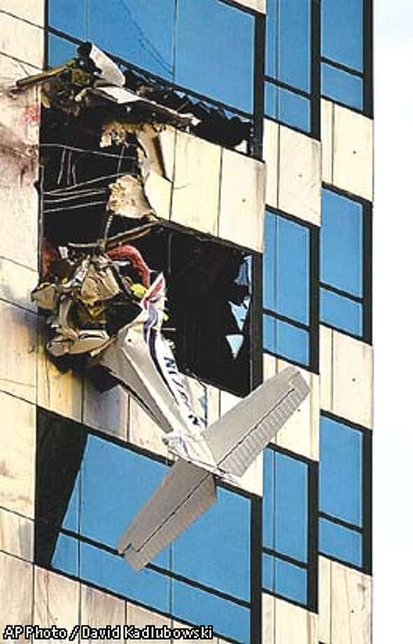 The fuselage of a single-engine plane dangles from the Bank of America building Saturday, Jan. 5, 2002, in Tampa, Fla., after a student pilot crashed into the downtown skyscraper following an unauthorized takeoff from St. Petersburg-Clearwater Airport. (AP Photo/The Tampa Tribune, David Kadlubowski) Photo: DAVID KADLUBOWSKI