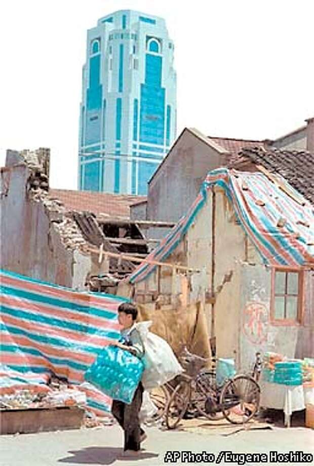 """An unidentified street vender walks past old houses marked with a Chinese character """"Chai"""" or """" Demolished """" in English, Monday, July 5, 1999 in a back alley in Shanghai. Old houses are being demolished in order to build new modern skyscrapers. (AP Photo / Eugene Hoshiko) Photo: EUGENE HOSHIKO"""