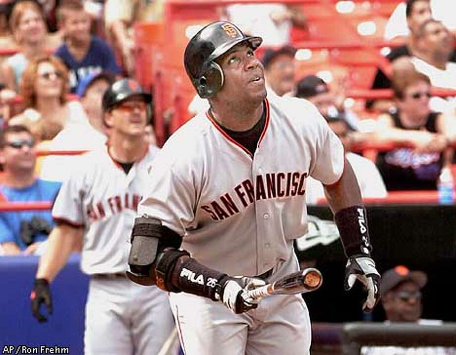 San Francisco Giants' Barry Bonds watches his 56th home run of the season in the fifth inning off New York Mets pitcher Kevin Appier, Monday, Aug. 27, 2001 at Shea Stadium in New York. On-deck batter Jeff Kent is at rear left.(AP Photo/Ron Frehm) Photo: RON FREHM