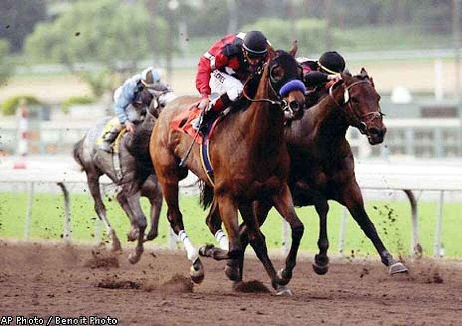 Wooden Phone, left, ridden by David Flores, pass Euchre, right, ridden by Garrett Gomez, to win the $200,000 San Pasqual Handicap on Saturday, Jan. 5, 2002, at in Arcadia, Calif. (AP Photo/Benoit Photo)