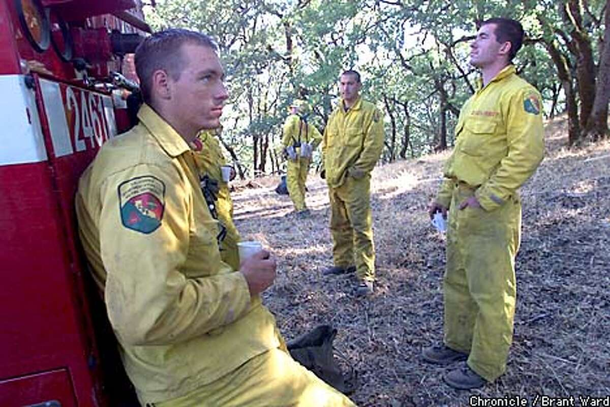 A tired and pensive group of firefighters took a break in the shade after a night of fighting the fires that raged because of the crashed aircraft nearby. Matt McDonald, left, and his fellow firefighters saw some ugly things they didn't want to talk about. The crew is from the Shasta-Trinity CDF group...Matt makes his home in Redding. By Brant Ward/Chronicle