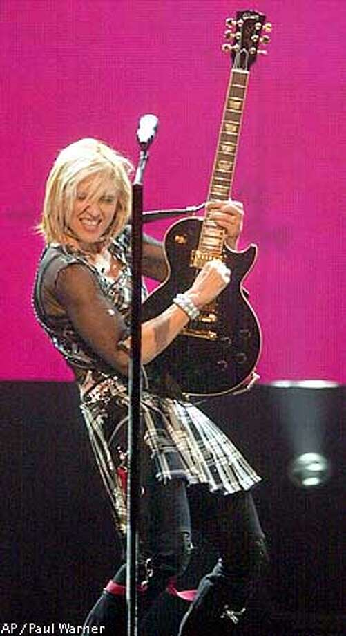 plays guitar during a stop on her Drowned World Tour at the Palace in Auburn Hills, Mich. on Saturday, Aug. 25, 2001 's Sunday concert at the venue, which is just miles from her childhood home of Rochester Hills, Mich. is to be broadcast live on HBO. (AP Photo/Paul Warner) Photo: PAUL WARNER