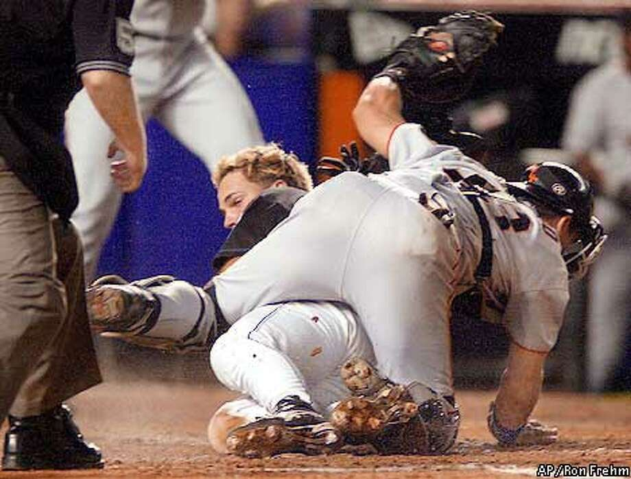 New York Mets' Mike Piazza is tagged out at the plate by San Francisco Giants catcher Benito Santiago in the sixth inning, Sunday, Aug. 26, 2001 at Shea Stadium in New York. Piazza tried to score from third on a sacrifice fly by Benny Agbayani to right fielder Shawon Dunston who made the throw to the plate. (AP Photo/Ron Frehm) Photo: RON FREHM