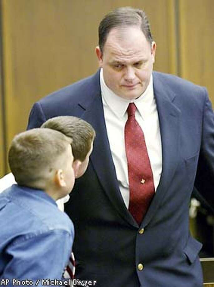 Thomas Junta, of Reading, Mass., right, speaks with his son Quinlan, 12, bottom left, and an unidentified boy, during a break in Junta's manslaughter trial Wednesday, Jan. 9, 2002, at Middlesex Superior Court, in Cambridge, Mass. Junta, 44, is accused of manslaughter in the death of Michael Costin, 40, who was alledgedly beaten by Junta following a youth hockey practice on July 5, 2000. (AP Photo/Michael Dwyer, Pool) Photo: MICHAEL DWYER