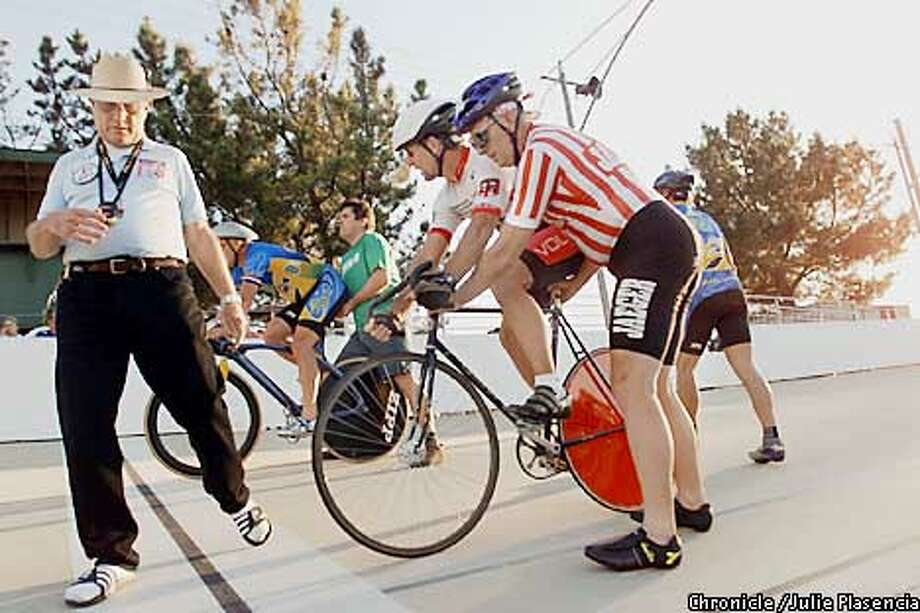 Official at the Hellyer park vellodrome, Peter Bohl, moves out of the way before cyclist take off on a timed race at northern california's only veledrome in San Jose. (JULIE PLASENCIA/THE CHRONICLE) Photo: JULIE PLASENCIA