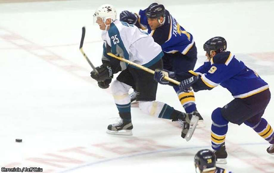 The Sharks' Vincent Damphousse tries to skate past Keith Tkachuk, top, and Scott Mellanby of the St. Louis Blues in the first period in which the Sharks trailed 3-0 at the Compaq Center in San Jose on Tuesday night. Photo by Jeff Chiu / The Chronicle. Photo: Jeff Chiu