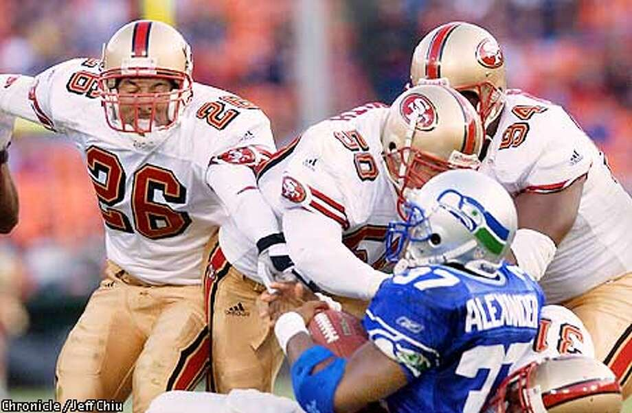 From left: Rashad Holman, Derek Smith, Dana Stubblefield, and Zack Bronson (bottom right) gang tackle running back Shaun Alexander of Seattle in the second quarter as the 49ers host the Seattle Seahawks in a preseason game on Saturday night at 3Com Park. Photo by Jeff Chiu / The Chronicle. Photo: Jeff Chiu
