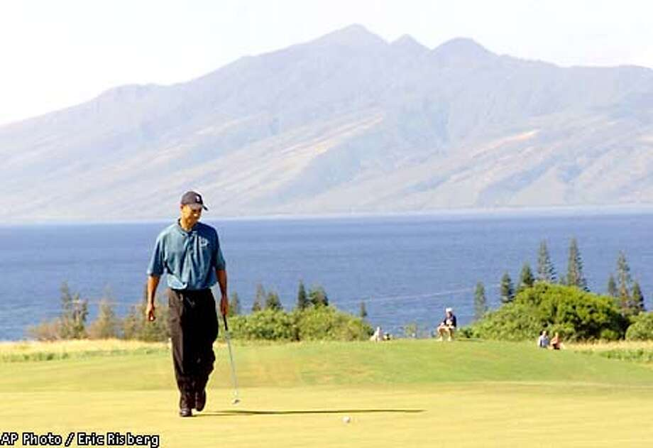 Tiger Woods looks over his putt that rolled up short on the third green of the Plantation Course during first round play of the in Kapalua, Hawaii Thursday Jan. 3, 2002. In the background is the island of Molokai.(AP Photo/Eric Risberg) Photo: ERIC RISBERG