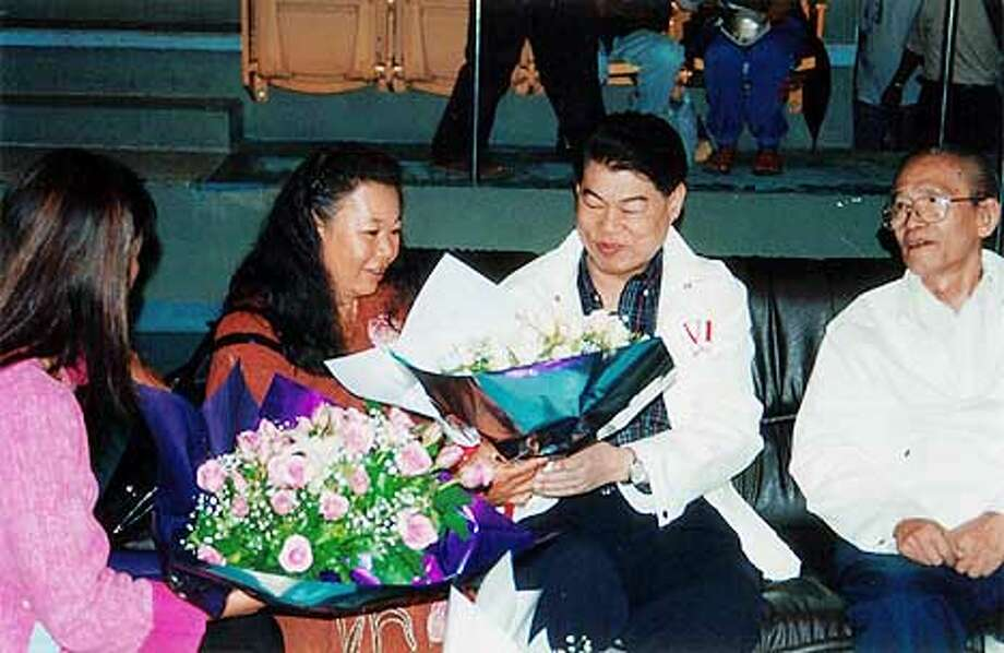 Salang Bunnag (right), head of the foundation sponsoring the giveaways, got flowers from AIDS patients' relatives. Photo by Rafael D. Frankel, special to the Chronicle