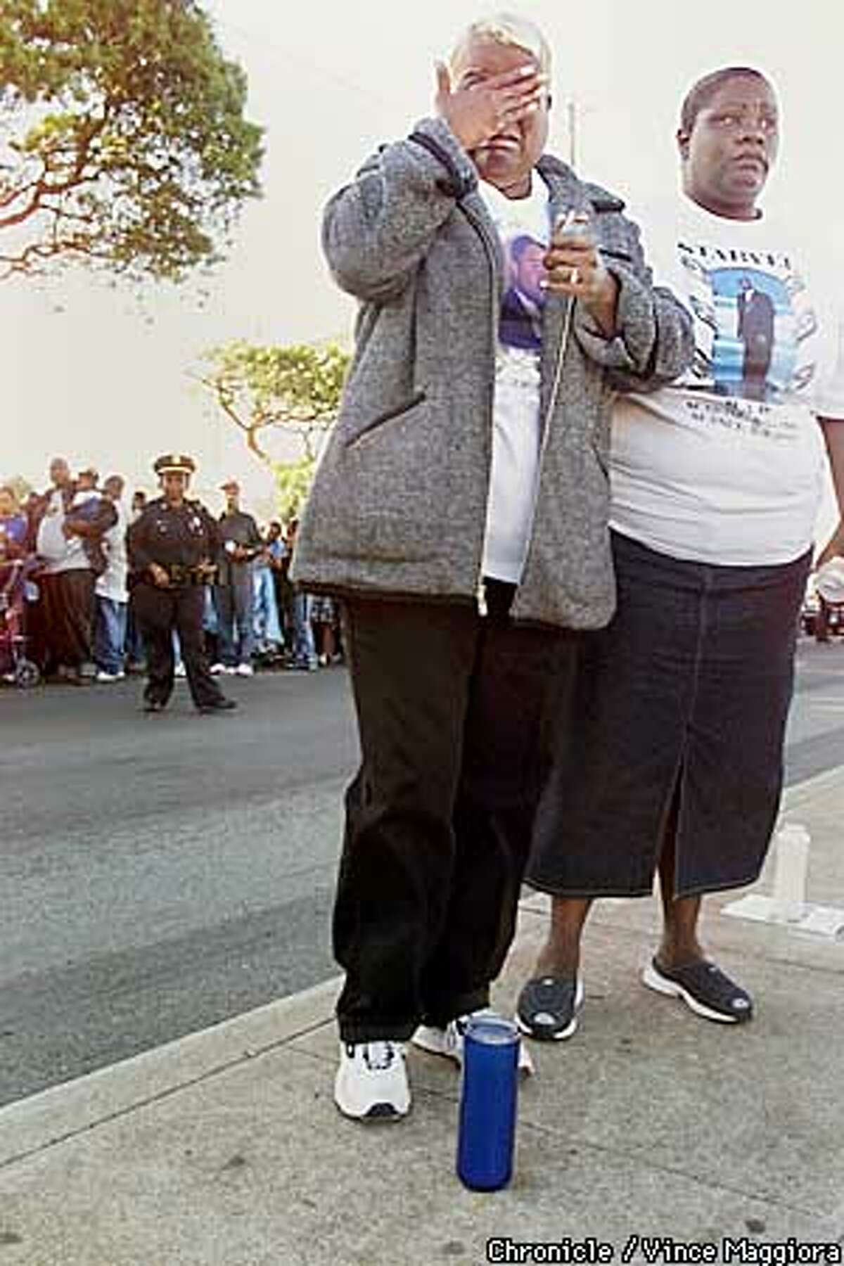 Jacalyn Pitcher with her hand on her face putting a candle down on 3 rd st. in hunters point for son Starvel Junious who was killed on may 3 2000 mothers and family march for murders of young black men. by Vince Maggiora