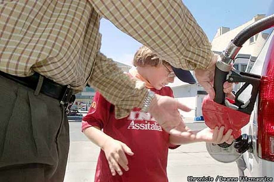 Eric Anderson, 8, from San Francisco, helps his father, Doug, pump $76.07 (40.9 gallons) worth of gas into the family Chevy Suburban at the Chevron station at Lombard and Laguna in San Francisco. CHRONICLE PHOTO BY DEANNE FITZMAURICE Photo: DEANNE FITZMAURICE