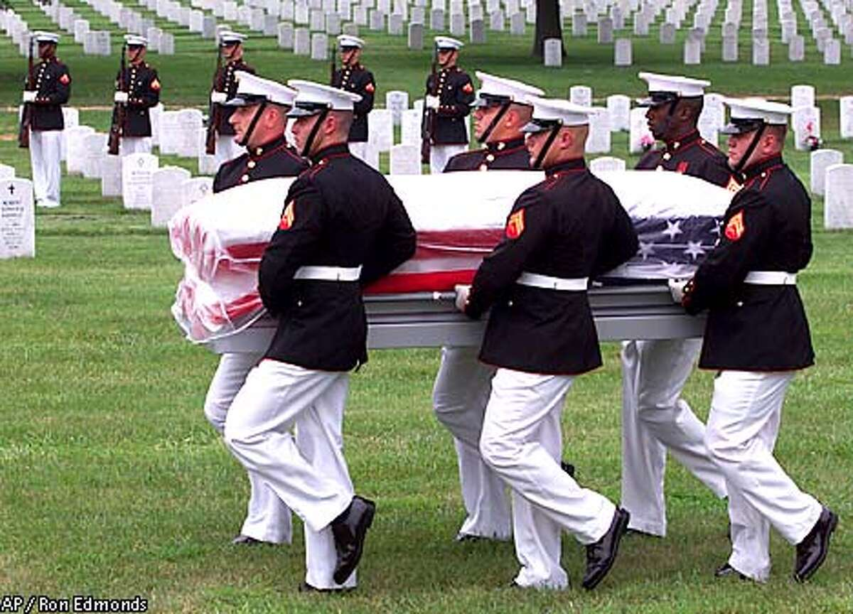 A Marine honor guard carries one of 13 World War II Marines killed during a 1942 raid on the Japanese-held Makin Atoll in the Gilbert Islands, during funeral services at Arlington National Cemetery in Arlington, Va. Friday, Aug. 17, 2001. The Marines' remains were discovered on the island nearly 60 years after they fell in battle (AP Photo/Ron Edmonds)