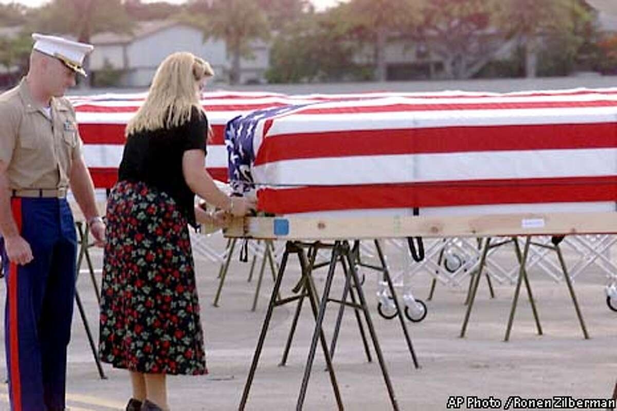 Maj. Chris Hughes stands by as Terilyn Stephens, 24, places a bouquet of anthuriums on the casket of one of 13 Marines killed in action on a South Pacific atoll during World War II at Hickam Air Force Base, Hawaii, Wednesday, Aug. 15, 2001. Stephens, of Valdez, Alaska, the 24-year-old great-niece of Cpl. Robert B. Pearson of Lafayette, Calif., placed anthurium flowers on one of the caskets as a gesture on behalf of the families of the 13. The 13 are among 19 Marines from the 2nd Raider Battalion who were killed during an Aug. 17, 1942, raid on the Japanese-held Makin Atoll, now known as Butaritari, in the Gilbert Islands. The 13 will be buried in a common area at Arlington National Cemetery in Virginia on Friday. The remains of the other six were previously returned to families for burial. (AP Photo / Ronen Zilberman)