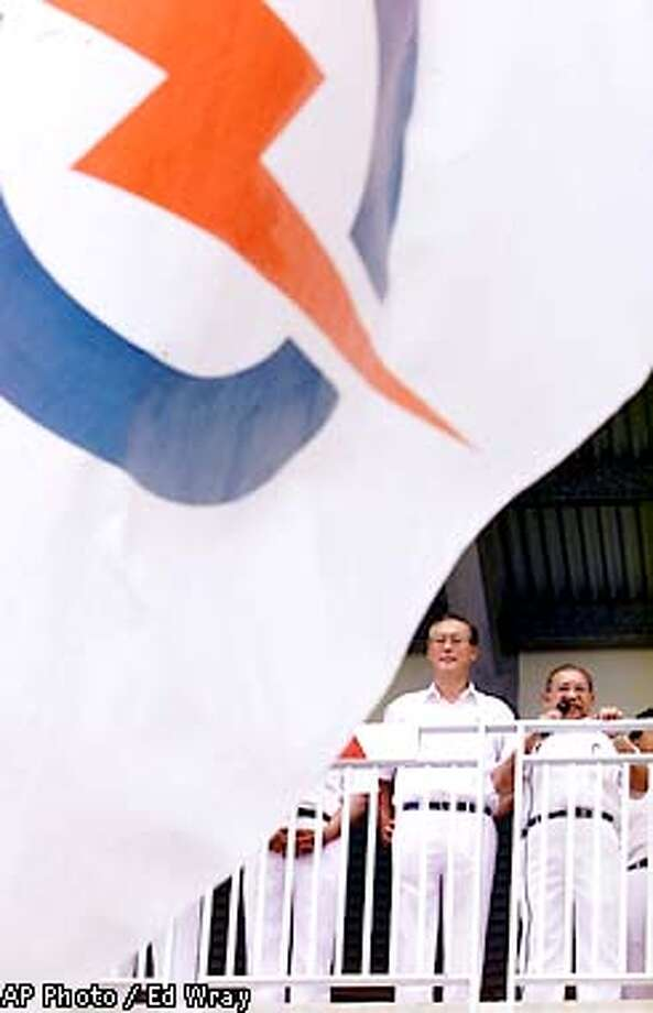 Singapore's Prime Minister Goh Chok Tong, second right, stands with unidentified People's Action Party (PAP) officials after learning that his district was not being contested by any other parties Thursday, Oct. 25, 2001, in Singapore. Flags bearing the PAP's signature lightning bolt waved throughout Singapore as the long-ruling PAP was returned to power when nominations closed Thursday as opposition candidates were not contesting enough seats to form a majority in the Parliament. (AP Photo/Ed Wray) Photo: ED WRAY