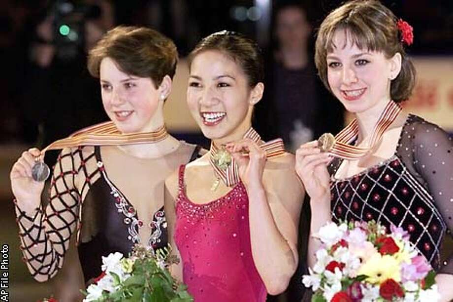 The medalists in the ladies competition at the Championships display their medals at the awards ceremony in Vancouver, British Columbia, Saturday, March 24, 2001. They are, from left, silver medalist Irina Slutskaya of Russia, gold medalist Michelle Kwan of the United States and bronze medalist Sarah Hughes also of the United States. (AP Photo/Amy Sancetta) Photo: AMY SANCETTA