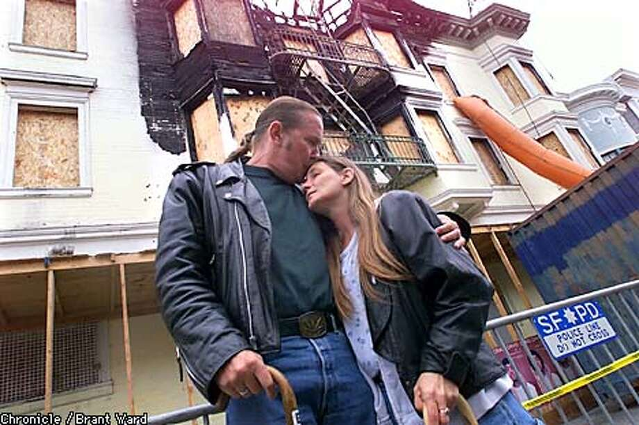 Paul Heaney kisses his wife Starla in front of their former home, the Raymond Hotel. They were burned out of the residential hotel some months ago and have been unable to find a permanent home. By Brant Ward/Chronicle Photo: BRANT WARD