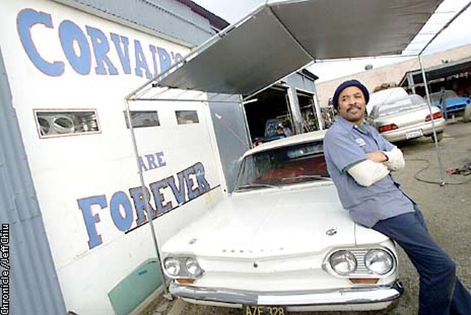 Mel Raven, owner of M&J Vairmart, stands next to one of his customers' Corvairs, a 1963 Monza convertible, at his shop in San Jose on Thursday afternoon. Raven, 54, fixes only Chevy Corvairs at his auto shop, owns six of his own, and belongs to a national Corvair club. Photo by Jeff Chiu / The Chronicle. Photo: Jeff Chiu