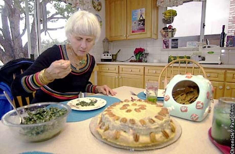 Elizabeth Bechtold sat down for a meal of kale salad, kale juice and a raw fruit torte at her Alameda home. Nearly everything Bechtold eats are raw vegetarian dishes.  PAUL CHINN/S.F. CHRONICLE Photo: PAUL CHINN
