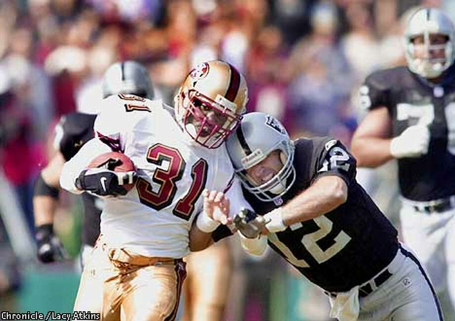 Rich Gannon puts a hit on Zack Bronson after Bronson's first quarter interception. The San Francisco 49ers played the Oakland Raiders during preseason action at 3com Park on Sunday, August 19, 2001. (Photo by Lacy Atkins/The San Francisco Chronicle) Photo: Lacy Atkins