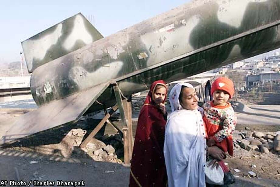 Kashmiri women walk past a replica of a missile built by a patriotic religious group aimed towards India in Muzafferabad, in Pakistan-controlled Kashmir, Saturday, Jan. 5, 2002. (AP Photo/Charles Dharapak) Photo: CHARLES DHARAPAK