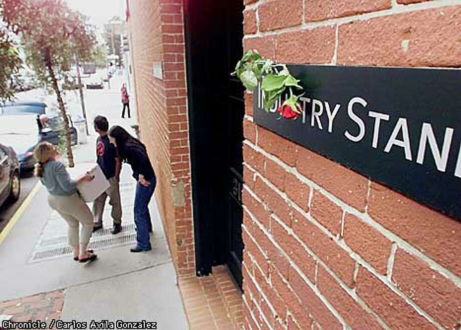 Employees at the Industry Standard in San Francisco, Ca., remove their possessions on Monday, August 21, 2001, from the company's headquarters after the company ceased publication of the magazine the previous week. Someone had placed a rose on the company's nameplate earlier in the day.  (Photo by Carlos Avila Gonzalez/The San Francisco Chronicle) Photo: CARLOS AVILA GONZALEZ