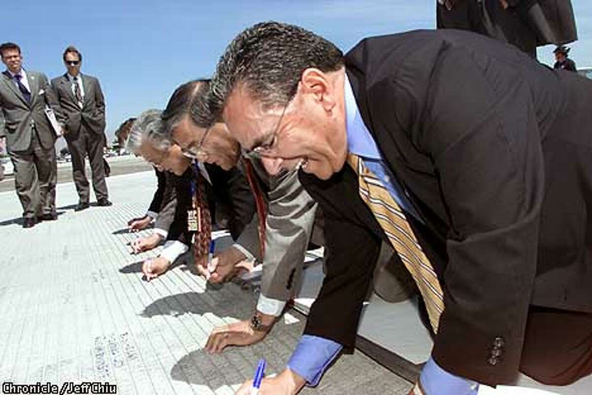 San Jose mayor Ron Gonzalez, foreground, former mayor of San Jose and current U.S. Secretary of Transportation Norman Mineta, second from right, and congressman Mike Honda sign the grounds of the new runway at a ceremony for the opening of the new runway at the San Jose International Airport on Monday afternoon. Photo by Jeff Chiu / The Chronicle.