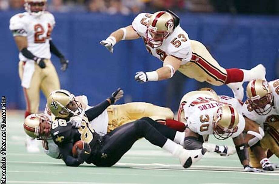 Jeff Ulbrich dives in to punctuate the tackle Derek Smith made on Willie Jackson as San Francisco 49ers beats New Orleans Saints 38-0 at the Superdome in New Orleans.  CHRONICLE PHOTO BY DEANNE FITZMAURICE Photo: DEANNE FITZMAURICE
