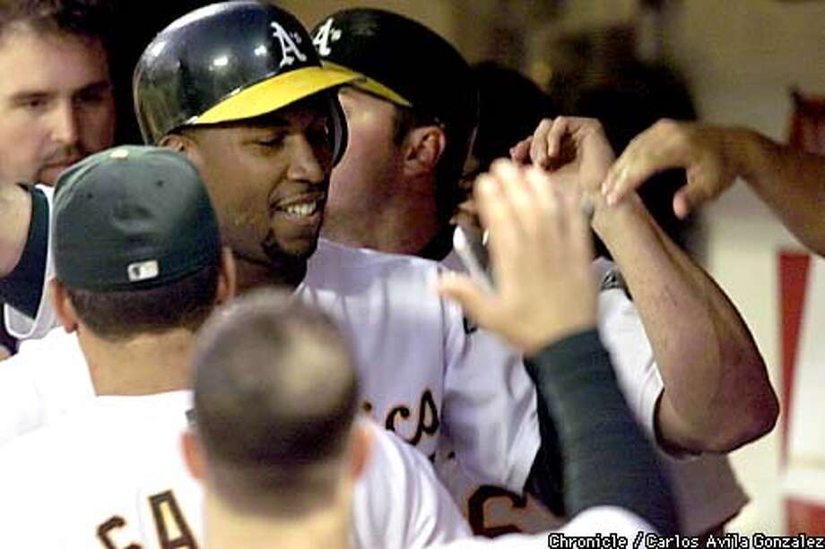Athletics' Jermaine Dye, is congratuled in the A's dugout following his two-run homer in the bottom of the 3rd inning against the Cleveland Indians at Network Associates Coliseum in Oakland, Ca., on Wednesday, August 22, 2001.  (Photo by Carlos Avila Gonzalez/The San Francisco Chronicle) Photo: CARLOS AVILA GONZALEZ