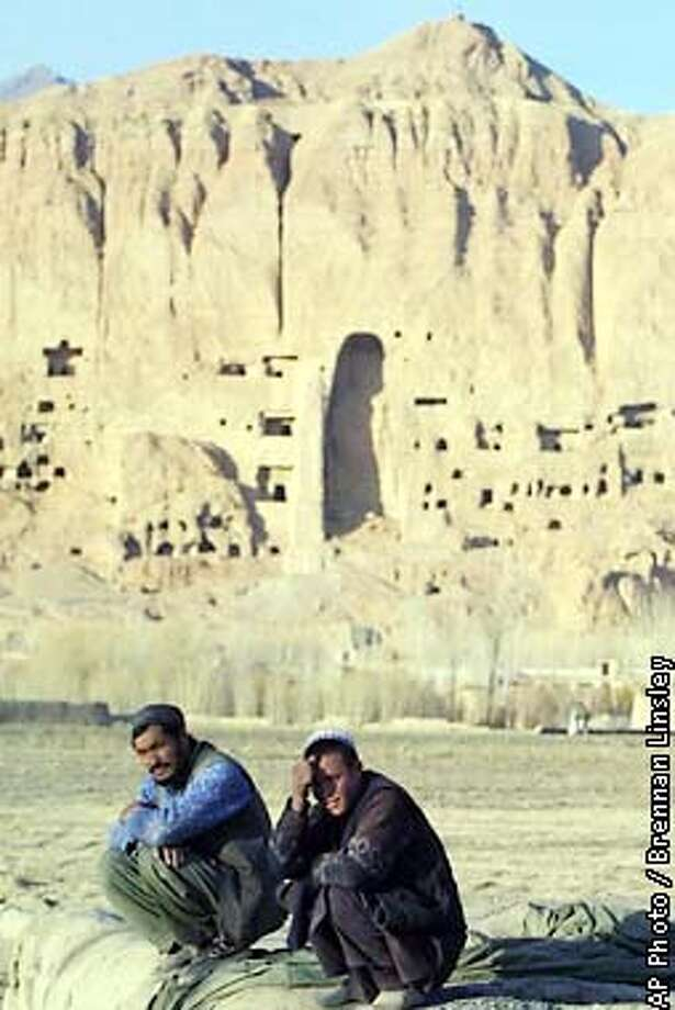 Afghan villagers sit watching the sun set, backed by the hole that was left behind after an enormous Buddha statue was destroyed by the former Taliban regime, in Bamiyan, northern Afghanistan, Wednesday, Jan. 2, 2002. The Buddha statues were part of a large network of smaller temples built into the side of the mountain around 1,500 years ago, when Bamiyan played a central role in the region's east-west trade route. The extremist view, not shared among most Islamic scholars butacted upon by the Taliban,held that the very existence of Buddha statues violated the Islamic code forbidding idolatry. (AP Photo/Brennan Linsley) Photo: BRENNAN LINSLEY