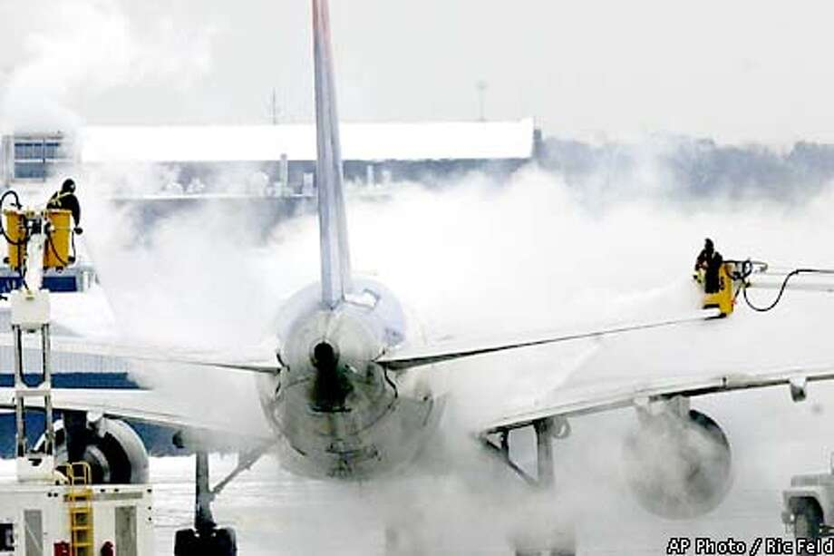 RECROPPED RETRANSMISSION--Workers are engulfed in spray as they de-ice a Delta Air Lines jet on the tarmac at Hartsfield Atlanta International Airport as snow continued to fall in the area Thursday, Jan. 3, 2002, in Atlanta. The airport was operating with two of the four runways and 20-30 flights an hour instead of the over one hundred flights an hour in normal circumstances. (AP Photo/Ric Feld) Photo: RIC FELD