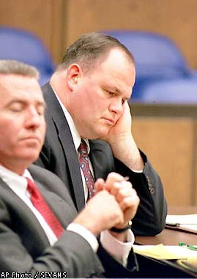 Thomas Junta, 42, right, leans his head on his hand as he listens to opening statements at his trial, Thursday, Jan. 3, 2002, in Middlesex Superior Court in Cambridge, Mass. Junta is charged with manslaughter in the July, 2000 beating death of Michael Costin. Costin died after an argument with Junta over rough play at a skating rink in Reading, just north of Boston. Junta's co-counsel John O'Connor is seen at left. (AP Photo/SEVANS, Pool) Photo: SEVANS