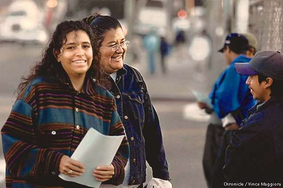 LtoR Patricia and Anamaria Loya talking with day labors on East 12th ,Oakland. They grew up in an activist household. So it may not be a surprise that the sisters head similar agencies, both of which offer legal and social services to members of the Latino community. Ana runs La Raza Central Legal in San Francisco, while younger sister Patricia heads the smaller but similarly named Central Legal La Raza in Oakland. Both say they are intent on improving the lives of thousands of low income Latinos in the Bay Area. BY Vince Maggiora Photo: VINCE MAGGIORA