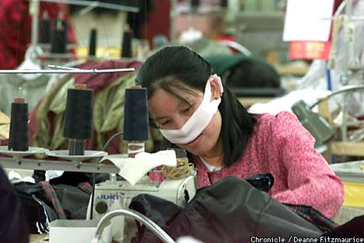 A garment factory worker at Wins of California garment factory in San Francisco wears a face guard to protect her from dust as she sews clothing. CHRONICLE PHOTO BY DEANNE FITZMAURICE