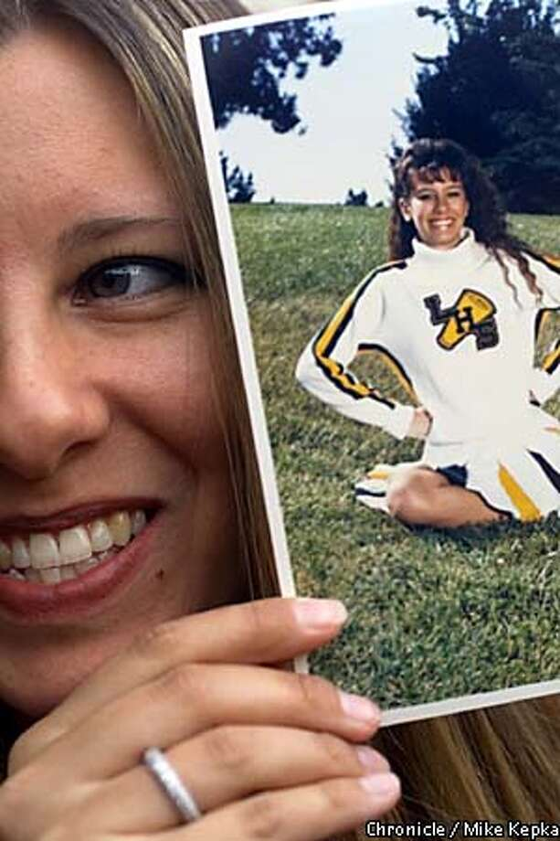 At her 10 year reunion, Cindy Pullman holds up a photograph of herself as a cheerleader her senior at Livermore High School. Cindy has been married for three years and is a stay at home mom for her 9-month-old daughter. BY MIKE KEPKA/THE CHRONICLE Photo: MIKE KEPKA