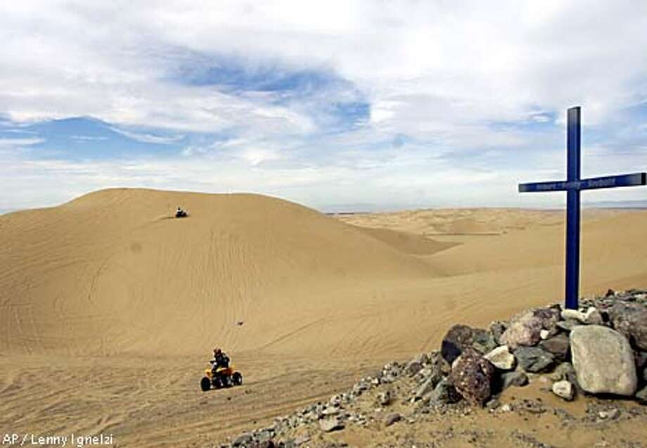 A cross in the Algodones Dunes marks a memorial for Robert 'Robby' Seebold, who was killed in an off-road vehicle accident. Associated Press photo by Lenny Ignelzi