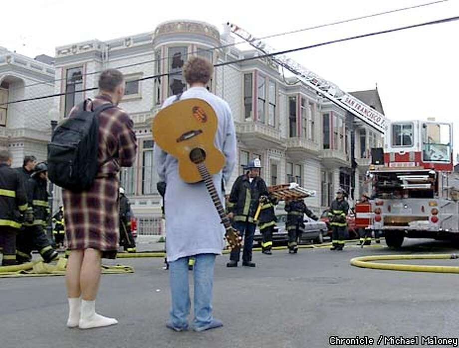 Displaced, shoeless roommates Lincoln Allen (left) and Aiden Sutton watch as firefighters work on their fire damaged apartment. Sutton managed to grab his most prized possession, his guitar before fleeing the building. Over 40 residents of a two story apartment complex at 20th Street and Capp Street in the Mission District were displaced from their homes in an early morning fire. CHRONICLE PHOTO BY MICHAEL MALONEY Photo: MICHAEL MALONEY