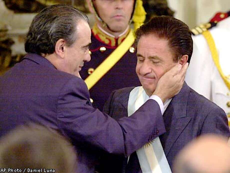 Eduardo Duhalde, 's new president, is congratulated by interim President Eduardo Camano, after receiving presidential attributes Wednesday, Jan. 2, 2002 at the Government House in Buenos Aires. Duhalde is expected Friday to outline his new economic plan, which could include breaking the country's decade-old currency peg, issuing $2 billion to $3 billion more negotiable bonds to add liquidity to the market, and easing banking withdrawal limits, local newspapers reported Wednesday. (AP Photo-Daniel Luna) Photo: DANIEL LUNA