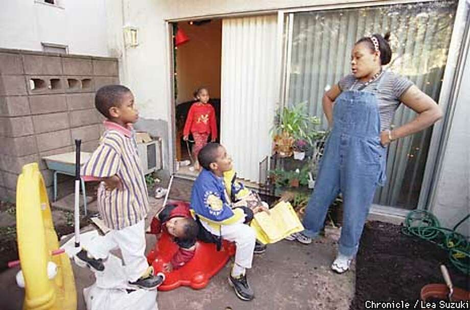 Keysha Clark talks to her children about cleaning their rooms in the backyard of their Walnut Creek home. From left: Deon Clark, 8; Frank Toney, 1; Jordun Hall, 5 (in doorway); Lamar Hall, 10; Keysha Clark. Photo by Lea Suzuki Photo: LEA SUZUKI