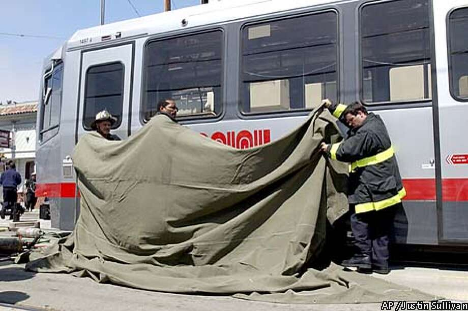 San Francisco Firefighters use a tarp to cover the body of a person who was struck and killed by a MUNI LRV on SAn Jose Avenue in San Francisco on Thursday August 16, 2001. Photo By Justin Sullivan Photo: JUSTIN SULLIVAN