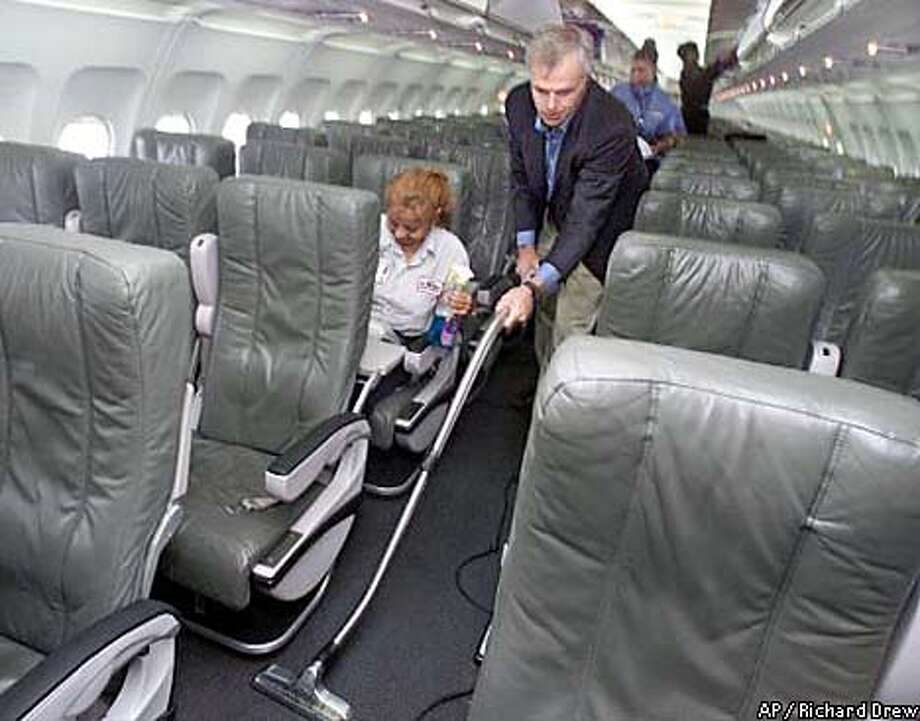 David Neeleman, founder and CEO of jetBlue Airways, wields a vacuum cleaner as he pitches in to help out the cleaning crew prepare an aircraft for the airline's inaugural trip to New Orleans, at New York's John F. Kennedy International Airport, July 26, 2001. Neeleman admits he is obsesses with the business. (AP Photo/Richard Drew)
