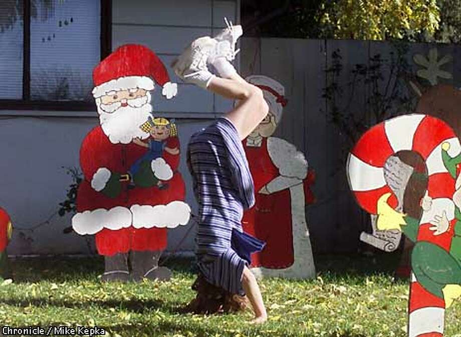 Nikki Murch , 8 of Dublin takes a brake from Christmas cookie baking at her Aunts house in Pleasant Hill to play the record breaking warm weather among the front yard holiday decorations. BY MIKE KEPKA/THE CHRONCLE Photo: MIKE KEPKA