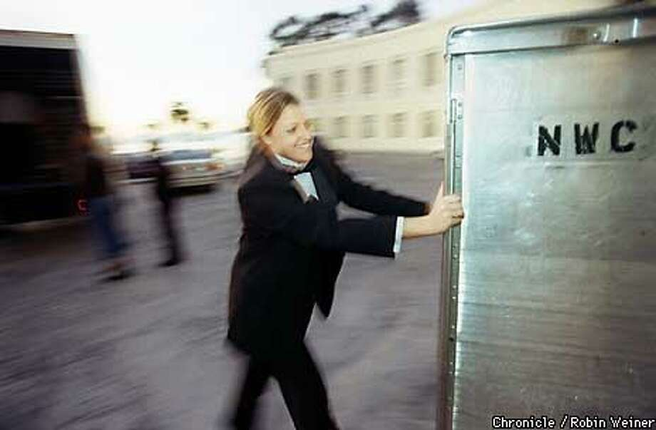 Jodi Harskamp, cq, who works in catering, pushes a Now We're Cooking food container for a holiday party at Treasure Island. Harskamp is contracted to work for a private party New Year's Eve, which she says will pay her a lot.  BY ROBIN WEINER/THE CHRONICLE Photo: ROBIN WEINER
