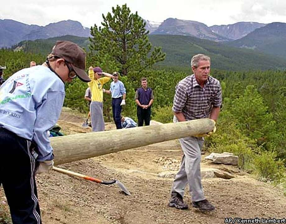President Bush helps to put down a support log while taking part in a trail rehabilitation project with YMCA camp member Karl Kraemer, in Rocky Mountain National Park Tuesday, Aug. 14, 2001, near Estes Park, Colo. (AP Photo/Kenneth Lambert) Photo: KENNETH LAMBERT