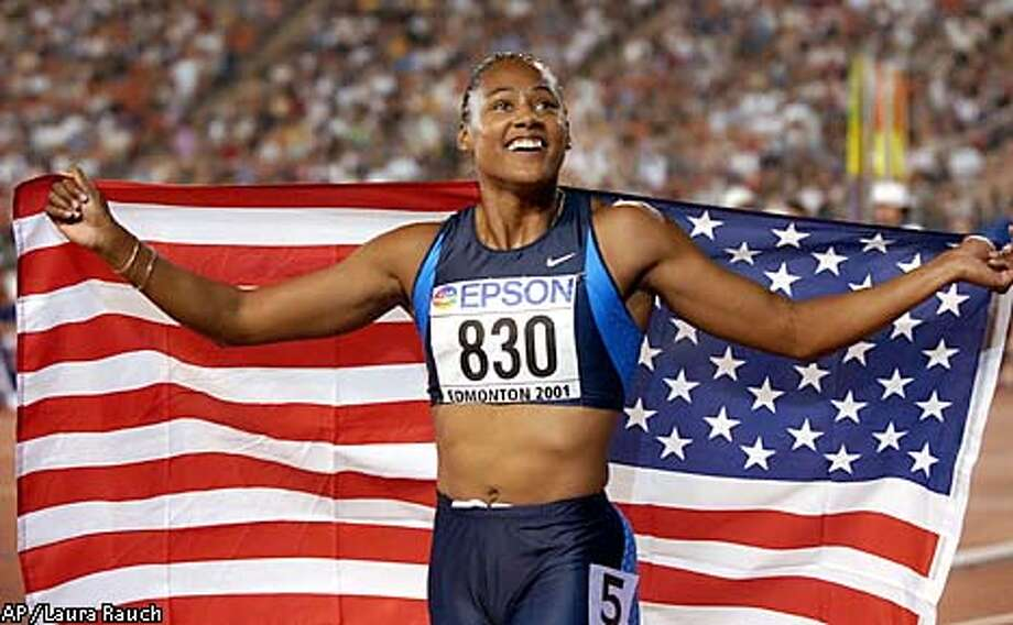 Marion Jones, of the United States, celebrates with an American flag after winning the gold medal in the women's 200 meters final Friday, Aug. 10, 2001, at the World Track & Field Championships at Commonwealth Stadium in Edmonton, Alberta. (AP Photo/Laura Rauch) Photo: LAURA RAUCH