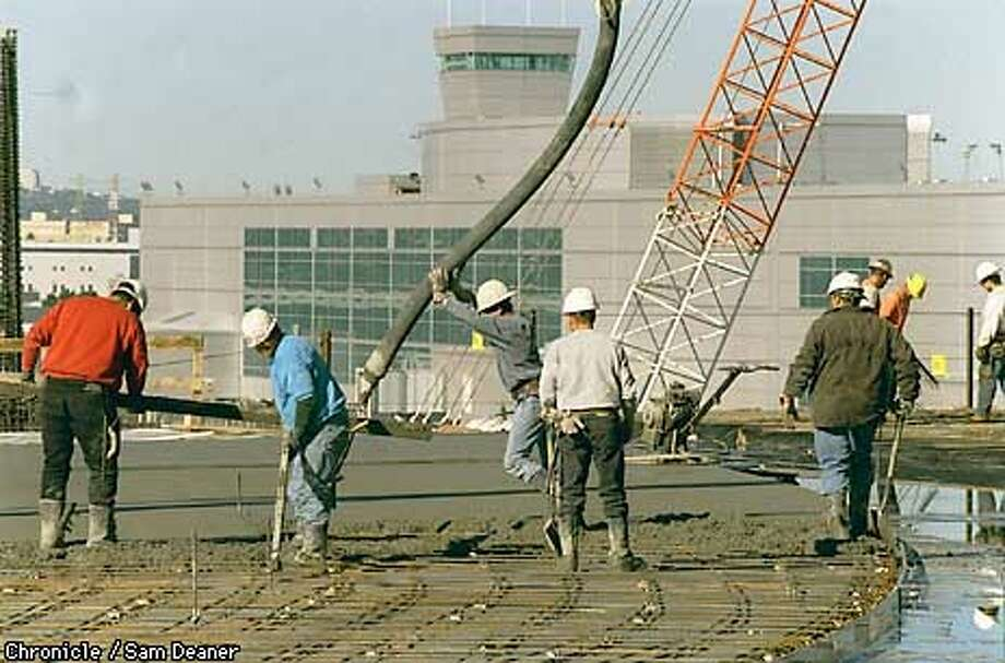 Workers pour concrete on at the new International terminal under construction at San Francisco International Airport Friday. CHRONICLE PHOTO BY SAM DEANER Photo: SAM DEANER