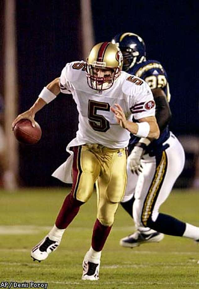 San Francisco 49ers quarterback Jeff Garcia (5) scrambles away from San Diego Chargers' Raylee Johnson in the first quarter Saturday, Aug. 11, 2001, in San Diego. Garcia gained 17 yards on the play. (AP Photo/Denis Poroy) Photo: DENIS POROY